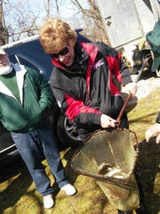 Roxanne Baumann helps at a fish restocking. The Muskellunge