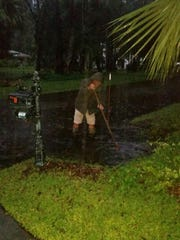 Mark Prickett tries to clear a drain while nearly knee-deep