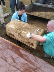 Caitlin Vogelsberg, a Michigan State University graduate student, and Jered Cornelison, an assistant professor of pathology at Western Michigan University, lift a coffin bearing the body of William Summerfield III from a grave in Marshall's Oakridge Cemetery.