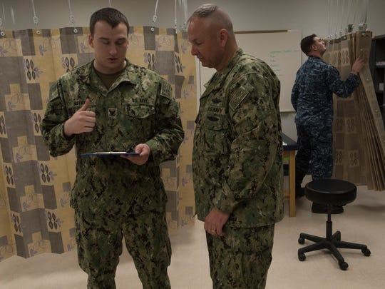 Navy Corpsman Petty Officer 3rd Class Travis Huffman, left, consults Wednesday on a patient with Cmdr. Ronald Fancher during clinic hours at the Naval Air Technical Training Center on board Pensacola Naval Air Station while Petty Officer 3rd Class Spencer Martin, right, prepares for the next patient.