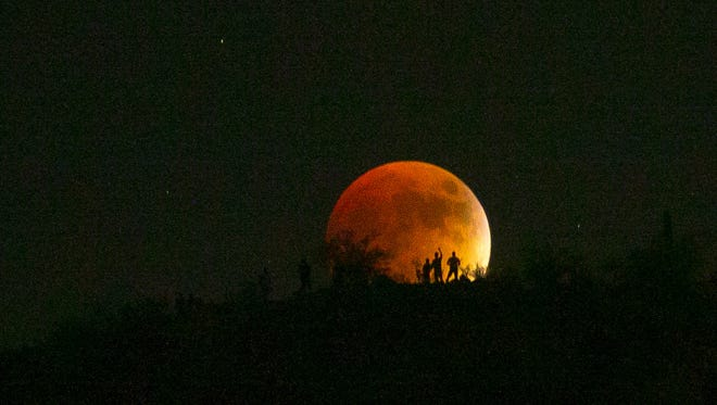 """Hikers look at the """"Super Blood Moon"""" seen from the Summit Trail at Piestewa Peak in Phoenix on Sunday, September 27, 2015. #superbloodmoon #supermoon"""