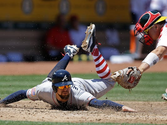 Atlanta Braves' Ender Inciarte, left, is tagged out by Oakland Athletics catcher Bruce Maxwell in the second inning of a baseball game, Sunday, July 2, 2017, in Oakland, Calif. Inciarte attempted to score on a hit by Braves' Brandon Phillips. (AP Photo/Ben Margot)