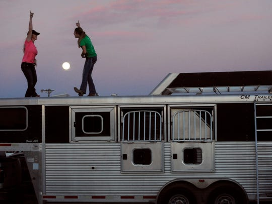 Sophomore Annie Metcalfe (left) and freshman Nevie Lord momentarily dance to music playing on Annie's phone while atop a livestock trailer Jan. 11. The two May High School students were competing in the Brown County Youth Fair.