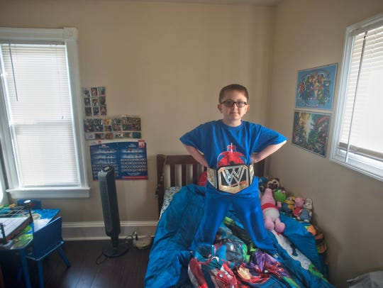 Riley O'Brien shows off his WWE belt in his bedroom