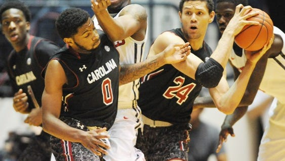 Mississippi guard Ladarius White, center, collides with South Carolina forward Michael Carrera (24) while guarding South Carolina guard Sindarius Thornwell (0) during an NCAA college basketball game in Oxford, Miss., Saturday, Jan. 10, 2015. (AP Photo/The Oxford Eagle, Bruce Newman) MAGAZINES OUT; NO SALES; MANDATORY CREDIT