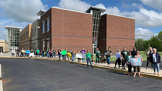 Malvern Elementary School teachers lined up the car turn around to give passing by elementary students a summer send off.