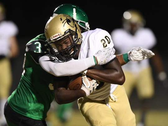 Easley's Caleb Hill (33) wraps up T.L. Hanna's Darius Blanding (20) at Easley on Friday, September 30, 2016.