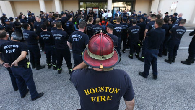 Houston firefighters gather for a briefing before going on a door-to-door survey of a neighborhood that was hit by floodwaters from Tropical Storm Harvey in Houston, Thursday, Aug. 31, 2017. The first responders are checking homes for any emergency needs of residents. (AP Photo/LM Otero) ORG XMIT: TXMO101
