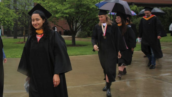 Monica Coronel, 23, walks through the Marist campus in the rain Saturday to receive her degree. She wants to be a surgeon.