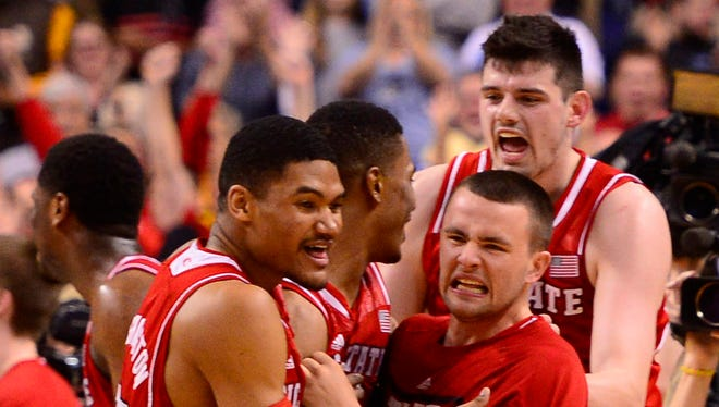 North Carolina State Wolfpack players celebrate after defeating Syracuse in the quarterfinals of the ACC tournament.