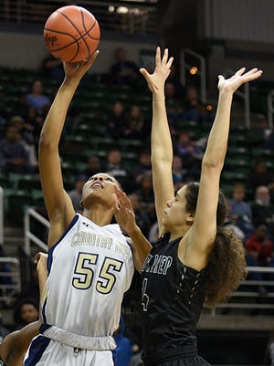 Detroit Country Day's Tylar Bennett (left), shown hitting a layup over Arbor Prep's Lasha Petree, was stellar in the paint during the final four.