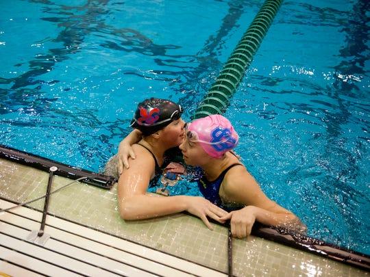 St. Clair swimmer Lola Laenen, left, hugs her friend,