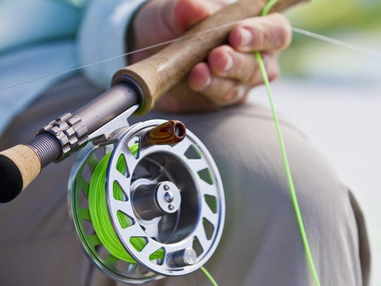 Writer Jack Ballard, of Red Lodge, Montana, carefully grasps his fly-fishing rod and reel Wednesday in Pine Island Sound while preparing for his next cast. Ballard was one of the members of the Outdoor Writers Association of America which met on Captiva.