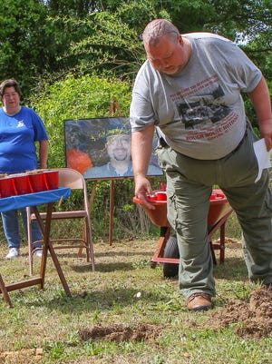 Jaye Shiflet, right, drops two cents near Joanne Shiflet, left, in the hole before planting a weeping willow tree, at a memorial Saturday for their son Charles David Carver at the family home in Starr.