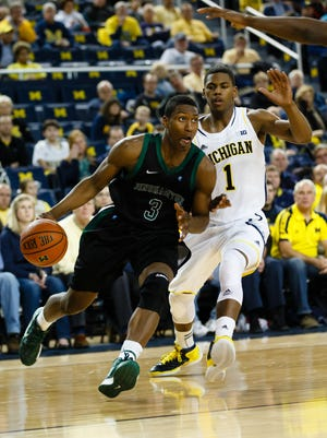 Binghamton University's Jordan Reed drives to the basket against University of Michigan forward Glenn Robinson III in the Crisler Center during the 2012-13 season.