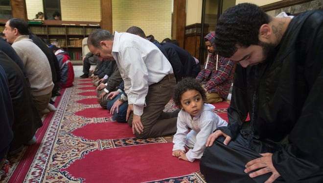 Two-year-old Aiden Abdelaziz, second from right, attends a December prayer service with his father Mohamed Abdelaziz right, at Dar Al-Hijrah Mosque in Falls Church, Va., site of an alleged hate crime this previous month.