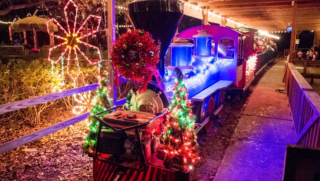 The tour train pulls into the train depot during the Safari of Lights at Zooisiana Zoo of Acadiana in Broussard, La., Sunday, Dec. 21, 2014. The Safari of Lights is held annually at the zoo during the holiday season with lighted displays near animal habitats.