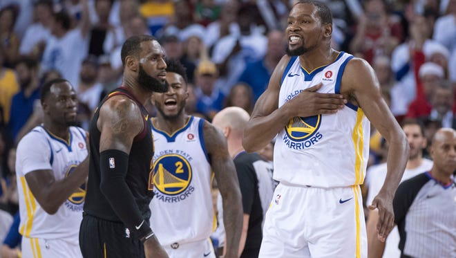 Golden State Warriors forward Kevin Durant (35) celebrates in front of Cleveland Cavaliers forward LeBron James (23) during the fourth quarter at Oracle Arena.
