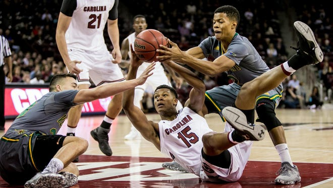 South Carolina's Gamecocks guard PJ Dozier (15) looks to pass over Vermont Catamounts guard Ernie Duncan (20) and Vermont Catamounts guard Trae Bell-Haynes (2) in the first half at Colonial Life Arena.