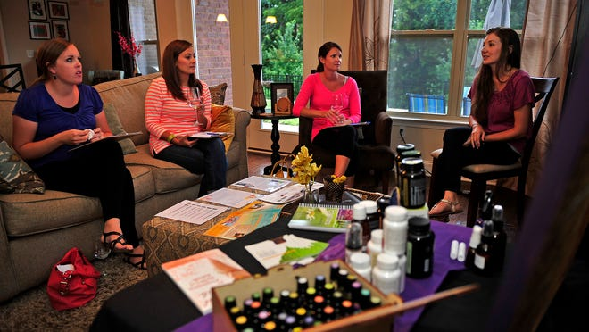 Brittany Webb, right, talks to Vanessa Smith, from left, Stacey Morris and Jennifer Walker in an Essential Oils 101 class at her home in Franklin<137>, Tenn., Thursday, July 17, 2014<137>.