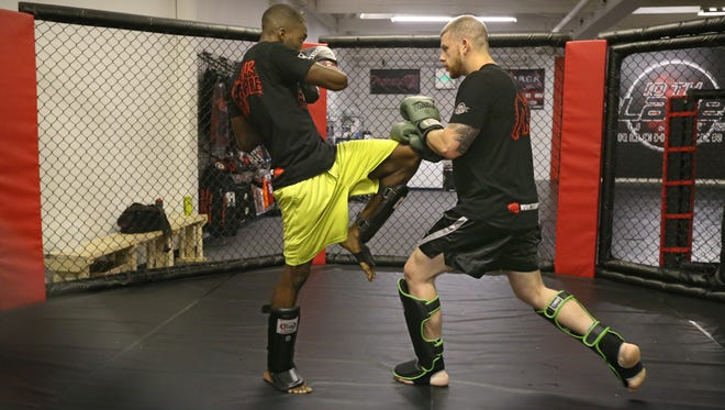 Malik Manon of Rochester, left, throws a knee at Josh Sackett of LeRoy, as they practice leg moves inside the octagon cage at Empire Academy of Combat Sports in Rochester.