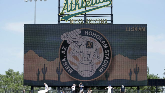 Fans sitting in the outfield at Hohokam Stadium in Mesa, Arizona.