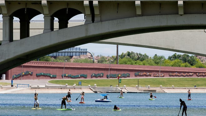 Stand-up paddle boarders enoy the weather at Tempe Town Lake on Friday, May 22, 2015.