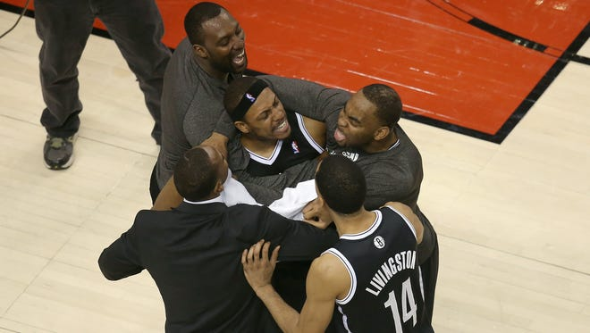 Brooklyn's Paul Pierce, center, celebrates after his block sealed the game with teammates Andray Blatche, rear left, Shaun Livingston, right, and Marcus Thornton after Game 7 against Toronto on Sunday.