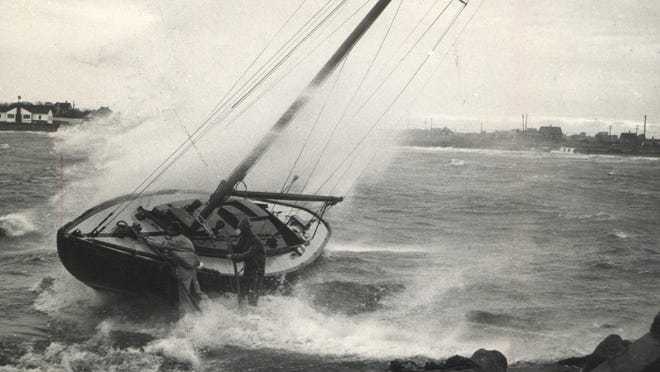 Boarding the sloop Brigadoon as it was pounded against rocks in Sakonnet Harbor by Hurricane Edna are friends of the owner, Paul Adams of Woodbridge, Connecticut, and Sakonnet. The two men removed the boat's compass and tiller.