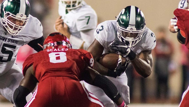 Michigan State running back LJ Scott runs the ball and is tackled by Indiana linebacker Tegray Scales in the first quarter Saturday in Bloomington, Ind.