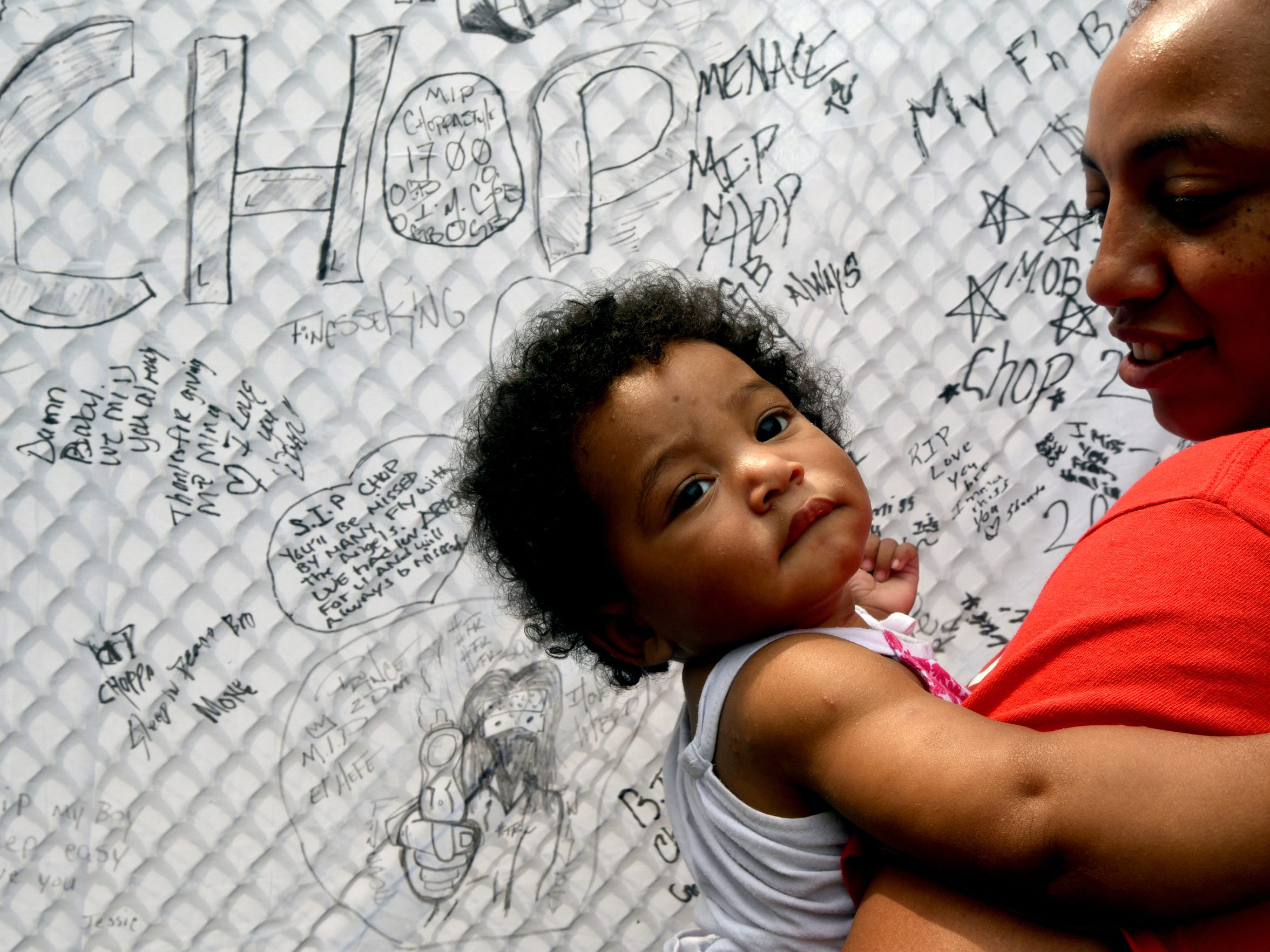 In North Camden, Dana Lorenzo holds daughter Zhane in front of a memorial sheet for the child's father, Johnathon Simmons, after the 19-year-old was shot to death in August 2015. Now, Lorenzo uses Facebook to warn teens to stay away from gang life.