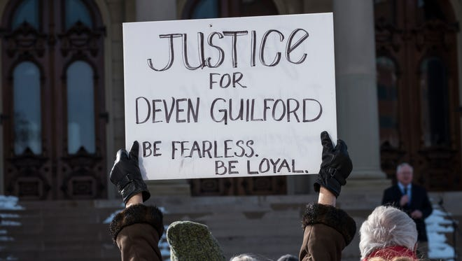 "This LSJ file photo shows a protester holding a sign calling for ""Justice for Deven Guilford"" during a rally at the Capitol in downtown Lansing marking the one-year anniversary of Guilford's 2015 shooting by an Eaton County sheriff's deputy."