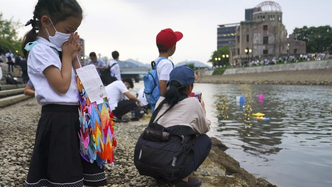 Saki Morioki, 5 years old, prays as paper lanterns float along the Motoyasu River in front of the Atomic Bomb Dome, Thursday, Aug. 6, 2020. in Hiroshima, western Japan. Japan marked the 75th anniversary Thursday of the atomic bombing of Hiroshima. The official lantern event was cancelled to the public due to coronavirus but a small group of local representatives released some lanterns. (AP Photo/Eugene Hoshiko)