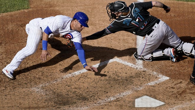 Chicago Cubs catcher Willson Contreras, left, is tagged out at home by Miami Marlins catcher Chad Wallach during the fourth inning in Game 2 of a National League wild-card series Friday in Chicago.