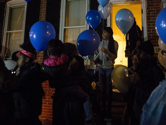 Friends and family of Richard Young hold balloons before