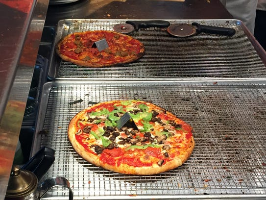 Pizzas right out of the oven await cutting