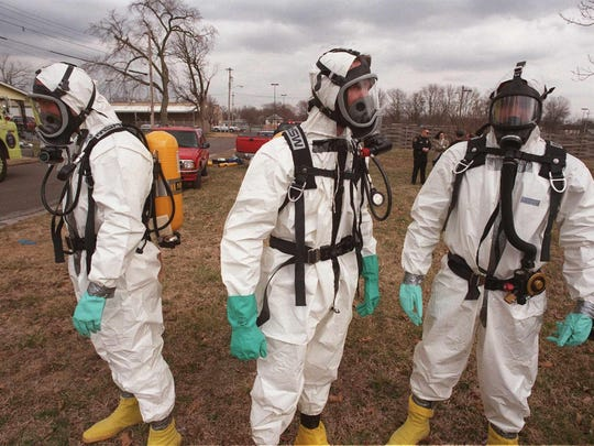 In this 1998 photo, Drug Enforcement Administration agents wait for fumes to be ventilated from a house before searching it for evidence of a meth lab.