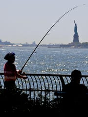 In this June 17, 2018, file photo, man fishes from the Battery City Park esplanade as temperature edge near 90 degrees in New York.