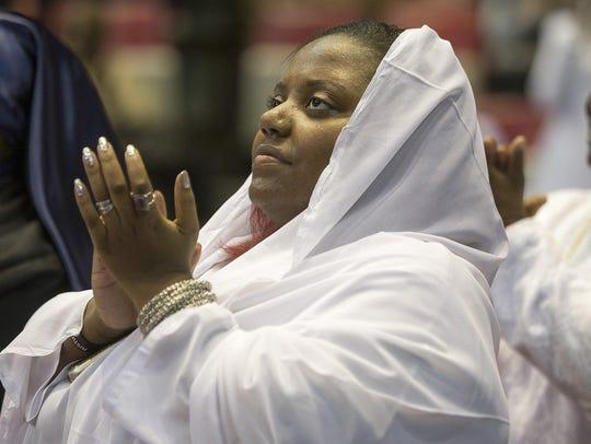 A woman claps during Minister Louis Farrakhan's speech