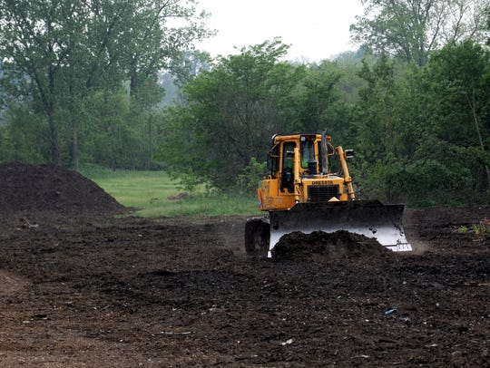 A bulldozer levels ground where a municipal compost