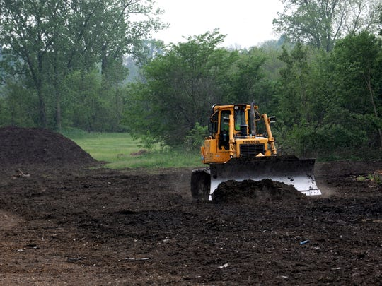 A bulldozer levels ground where a municipal compost site has been created on South Ewing Street in Lancaster.