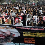 Shiite Muslims take part in a rally Sunday to condemn the execution of Saudi Shiite cleric Sheikh Nimr al-Nimr, in Lahore, Pakistan. Some nations have followed the Saudis' lead in severing or downgrading ties with Iran, while others have offered words of caution.