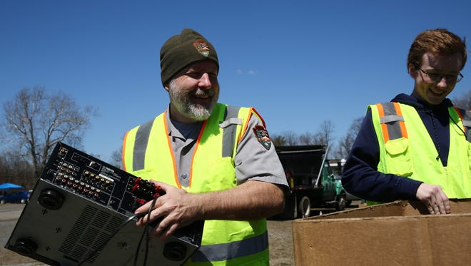 Mike Riegle of the National Park Service, left, and his son Owen load part of a computer into a box on Saturday. They were collecting electronics to go to E-Waste.