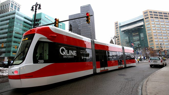One of the QLINE streetcars makes its way on Woodward Avenue through Campus Martius in Detroit on Tuesday, Dec. 13, 2016. The streetcar was being pulled by a tow truck during most of its initial test run on the tracks, but ran on its own electric power for a brief spin around Campus Martius on the southern end of its route.