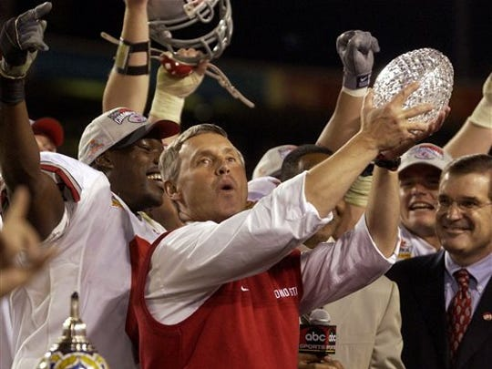 FILE - In this Jan. 3, 2003, file photo, Ohio State coach Jim Tressel holds up the colege football national championship trophy after Ohio State beat Miami 31-24 in two overtimes in the Fiesta Bowl in Tempe, Ariz. Tressel was selected for induction to the College Football Hall of Fame Friday, Jan. 9, 2015. (AP Photo/Paul Sakuma, File)