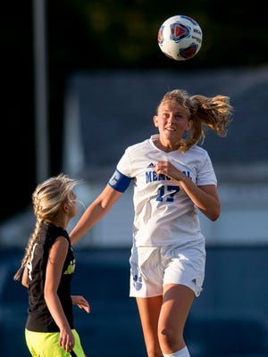 Memorial's Grace Lensing (17) heads the ball over North's Avery Tillsworth (4) during the North Huskies' game against the Memorial Tigers at Memorial High School in Evansville, Ind., on Wednesday, Sept. 6, 2017. Memorial won 5-0.