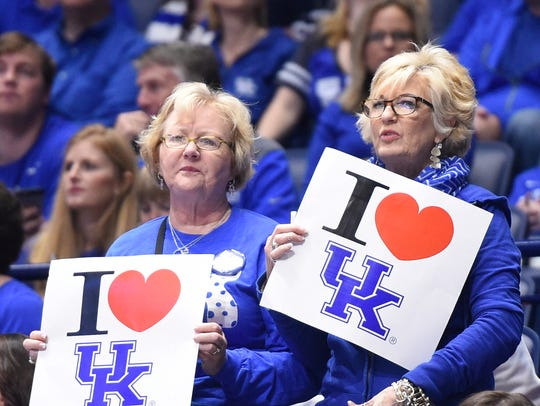 Two Kentucky fans show their support in a sea of blue