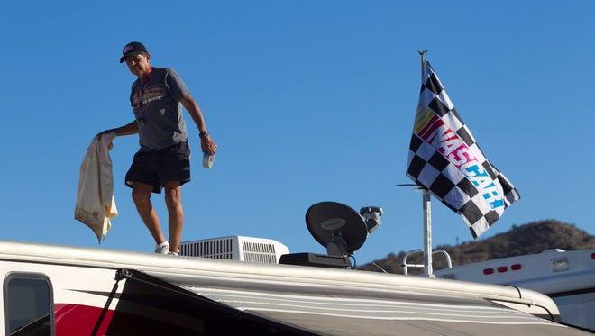 Bob Renteria, of Burbank, California, walks on top of his RV in the RV parking area at Phoenix International Raceway in Avondale on Nov. 5, 2014.