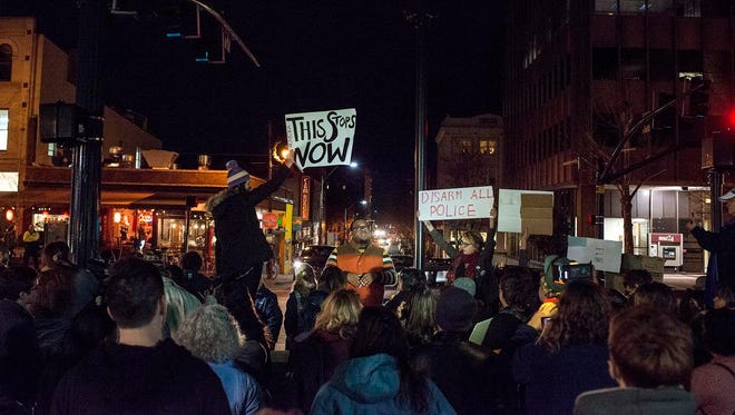 """Keith Knox, center, a UNC-Asheville student, speaks to protesters in Pack Square in Asheville during a demonstration Thursday night against the decision not to indite a white New York City police officer after Eric Garner, a black man, died during an arrest that involved a chokehold. Knox said he came because he has to stand with people like himself. """"I'm out here because I am Michael Brown; I am Eric Garner,"""" he said. The protest came just nine days after a similar protest about the Ferguson decision not to indite another white police officer after the fatal shooting of Michael Brown, an unarmed 18-year-old black man. About 100 people gathered to hold signs, chant and speak together in the city center on Thursday."""