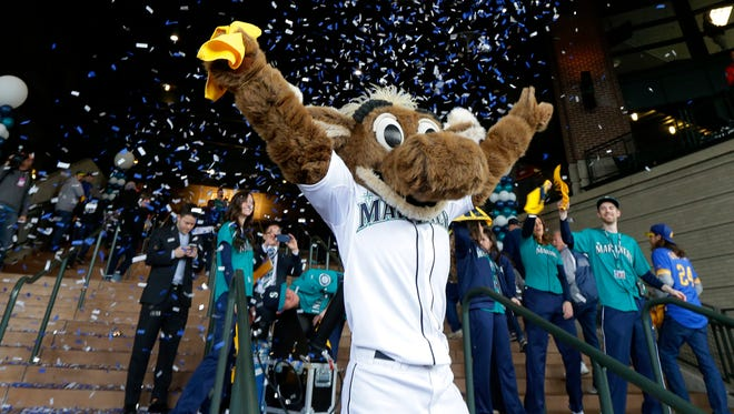 Moose, the Seattle Mariners mascot, welcomes the first fans through the gates as confetti flies behind him before an opening day baseball game between the Seattle Mariners and the Los Angeles Angels, Monday, April 6, 2015, in Seattle.